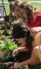 Besides a fashion show, Savannah Harmon and the girls planted pink petunias to show models could get dirty, too.