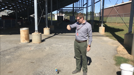 Hillcrest High physics teacher Scott Buhr drops an Astro Blaster next to the school's football stadium, where his class set a world record for a Galilean cannon shot. Look closely above and to the left of the balls on the ground to see the tiny red ball that has been shot.