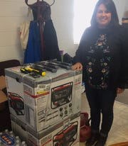 Amie Crawford poses with some of the more sizable donations for Florida residents: two brand new generators.