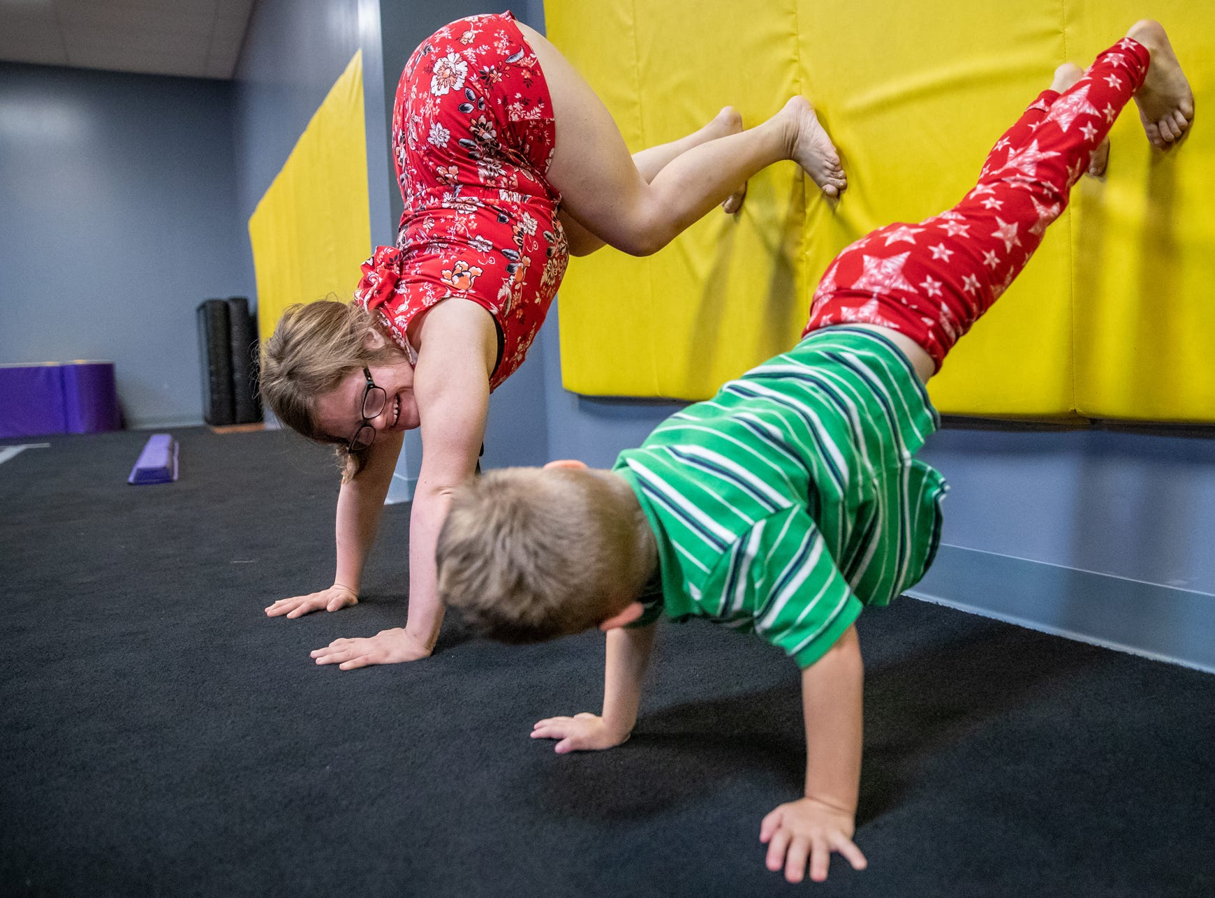 """Mickey Deputy demonstrates a handstand to Max Black, 4, of Franklin, Ind., at Style Dance Academy in Franklin, Ind., on Tuesday, Oct. 9, 2018. """"It's really fun because this is my dream job,"""" said Deputy."""