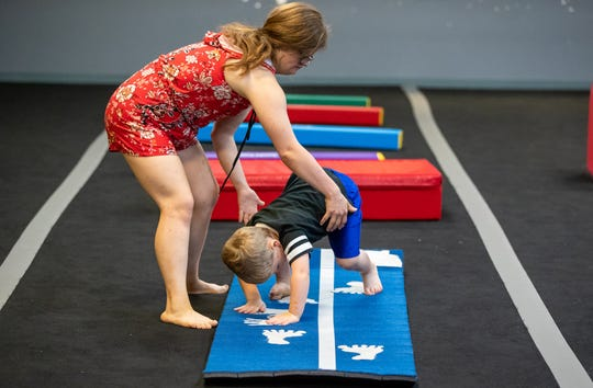 During the obstacle course section of the class, Mickey Deputy helps Owen Riley, 3, cartwheel over a foam mat at Style Dance Academy in Franklin, Ind., on Tuesday, Oct. 9, 2018.
