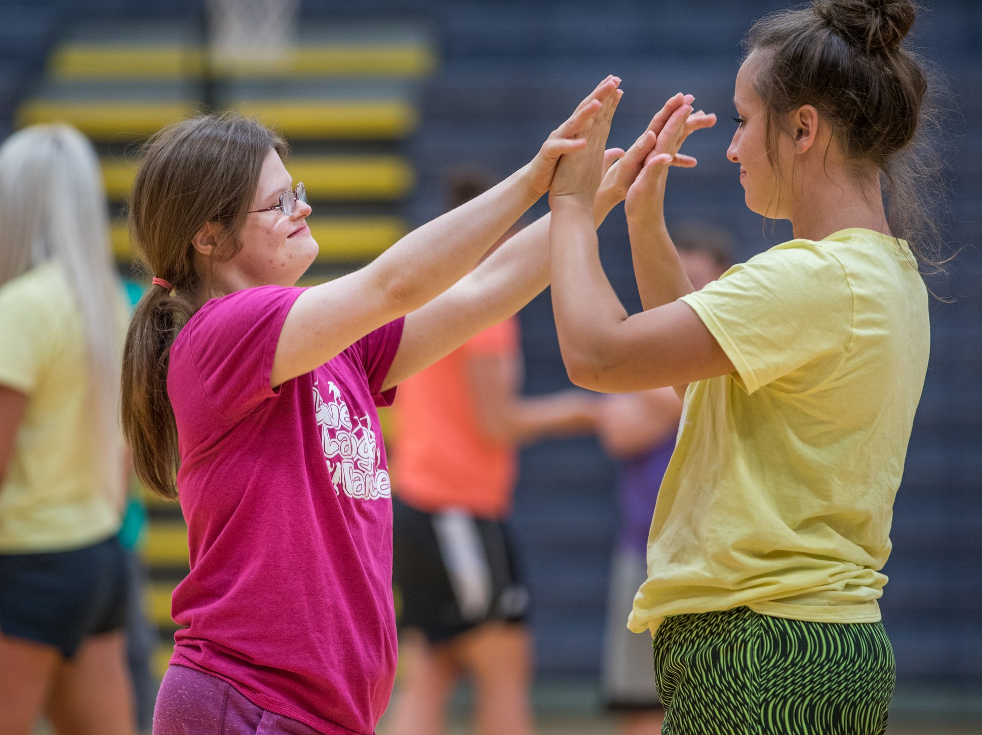 """Mickey Deputy (left) and her dance partner, Kelsey Edington, a volunteer, cheer after a dance routine during Live Laugh Dance on Tuesday, July 10, 2018. """"She just has the biggest personality,"""" said Edington. """"She's super sassy and makes me laugh."""""""
