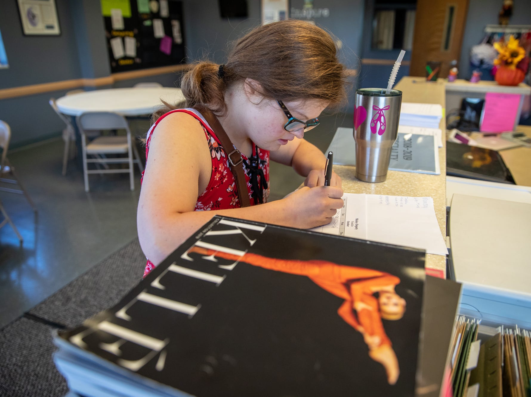 After catching a ride to work with fellow instructor Emily McCullough, Mickey fills out her schedule and timesheet at Style Dance Academy in Franklin, Ind., on Tuesday, Oct. 9, 2018.