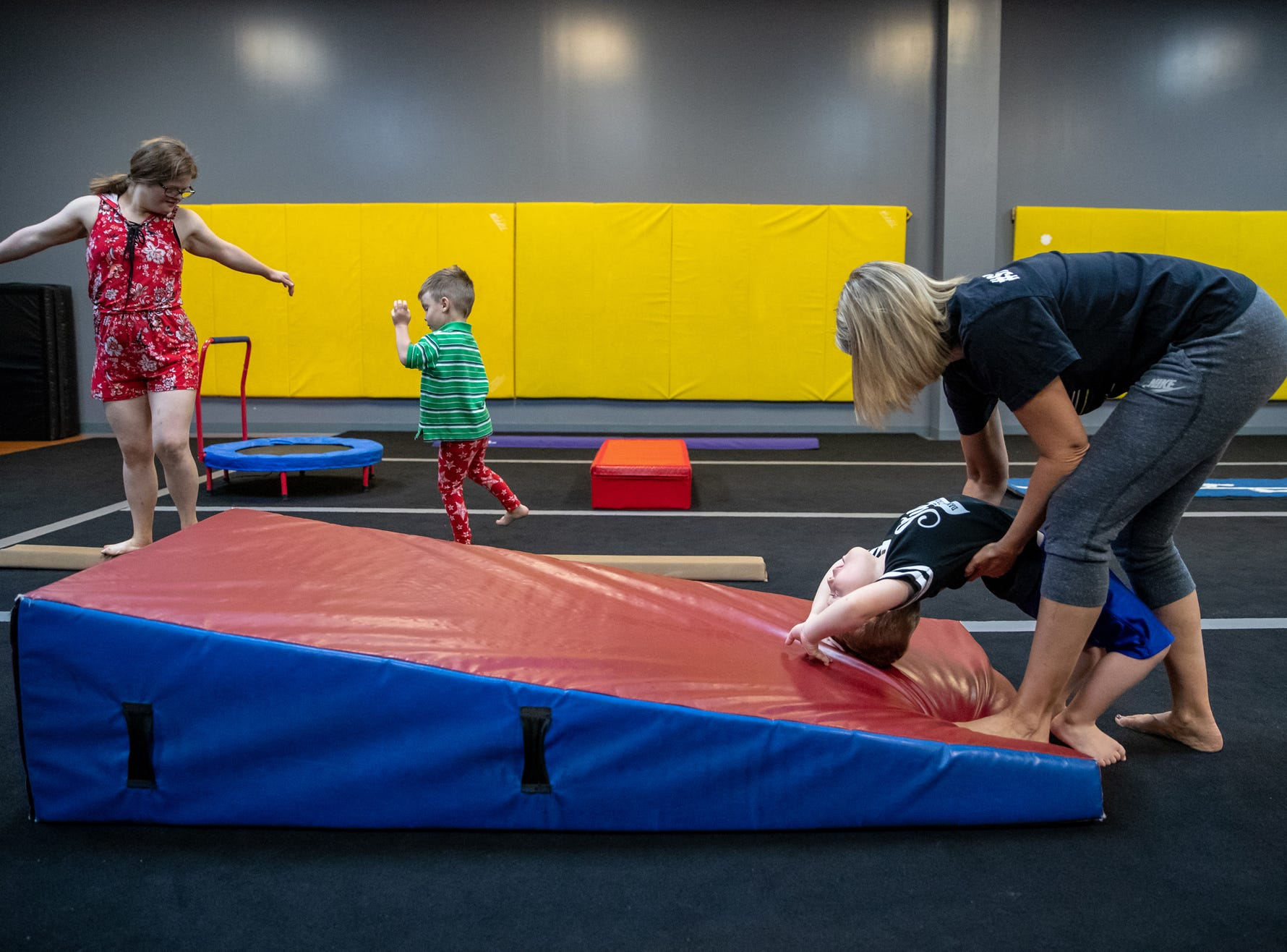 As instructor Emily McCullough helps Owen Riley, 3, with a backbend, Mickey Deputy walks a balance beam with student Max Black, 4, during gymnastics class at Style Dance Academy in Franklin, Ind., on Tuesday, Oct. 9, 2018.