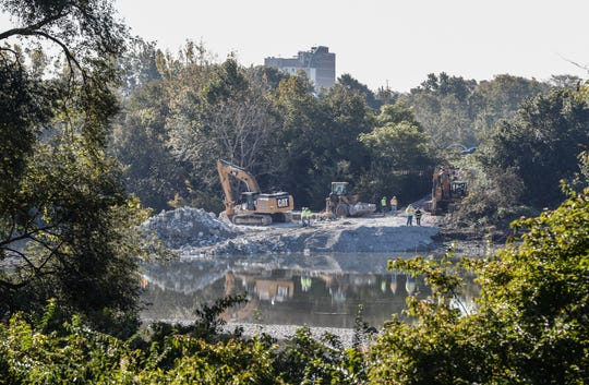 Work crews repair the Riverside Park dam near 16th Street on Thursday, Oct. 18, 2018. Erosion is believed to be the cause for the hole that allowed water to rush underneath the dam, which was built 1915-1917. The building of the levee after the Great Flood of 1913 was the reason Indianapolis' oldest brick home — built by one of its first settlers, Samuel McCormick — was razed in 1914. The home stood near the dam.