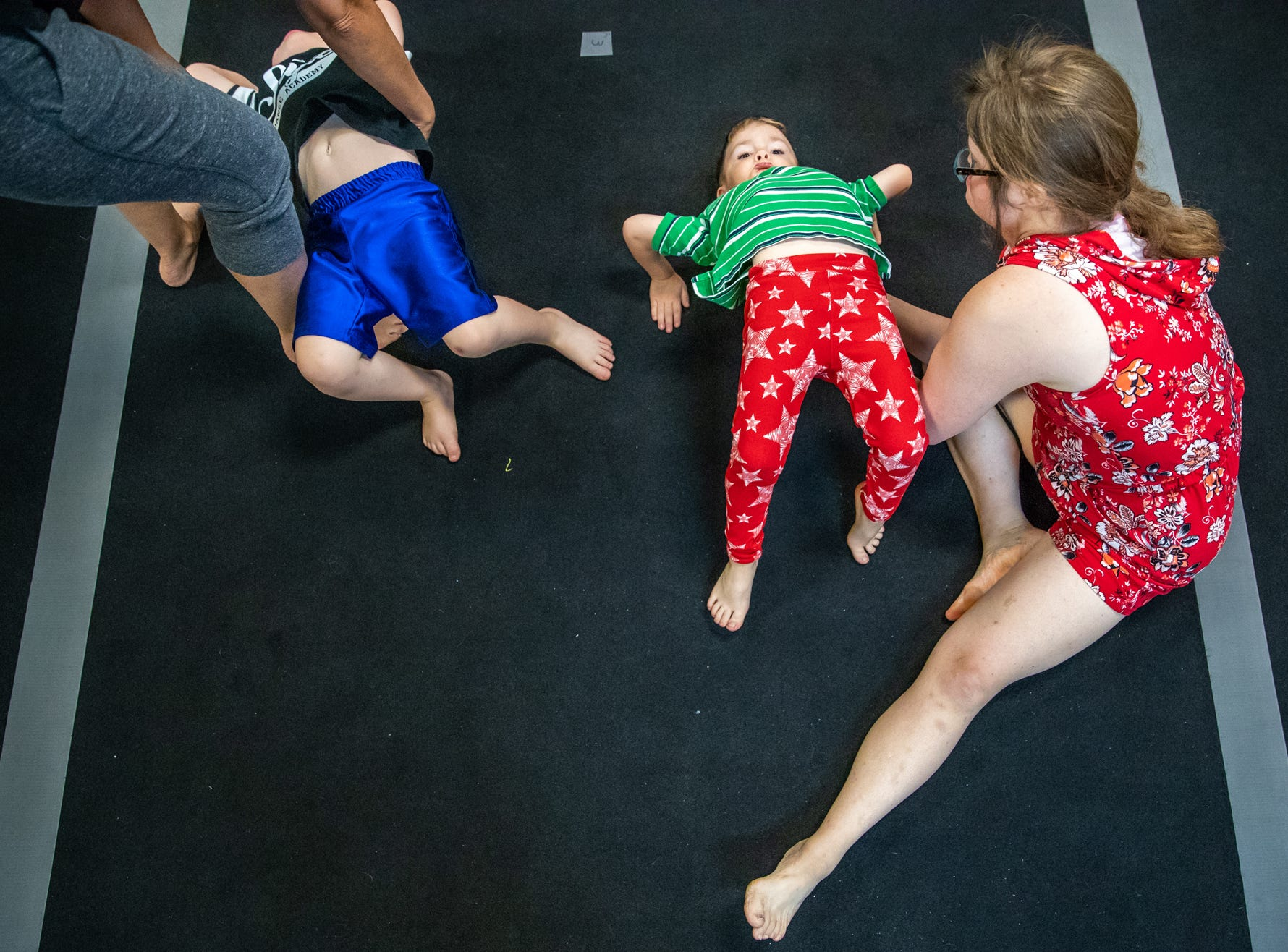"""Mickey Deputy, as well as fellow instructor Emily McCullough, help students Max Black, 4, and Owen Riley, 3, work on their backbends during gymnastics class at Style Dance Academy in Franklin, Ind., on Tuesday, Oct. 9, 2018. """"Nice!"""" said Deputy, as she helps Black arch his back. """"Hands back, hands back."""""""