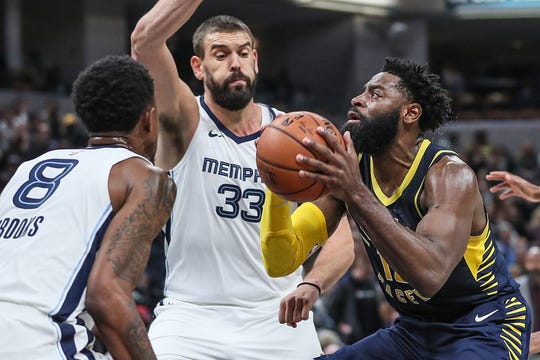 Indiana Pacers guard Tyreke Evans (12) goes to the basket under defense from Memphis Grizzlies guard MarShon Brooks (8) and center Marc Gasol (33) during the first half of the season opener at Banker's Life Fieldhouse in Indianapolis, Wednesday, Oct. 17, 2018.