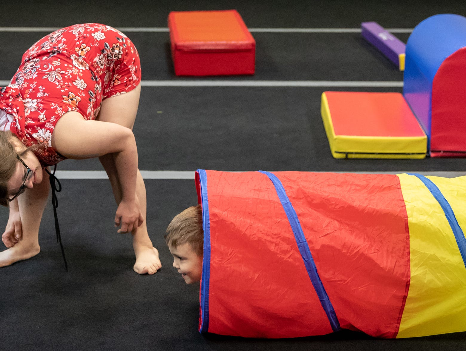 Mickey Deputy waits for student Max Black to exit a tunnel during the obstacle course section of gymnastics class at Style Dance Academy in Franklin, Ind., on Tuesday, Oct. 9, 2018.