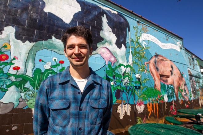 Thomas Agran, of Iowa City, stands in front of a mural he painted on Thursday, Oct. 18, 2018, outside New Pioneer Co-Op at 22 S. Van Buren Street. Agran's 2013 mural was the first one he completed in Iowa City.