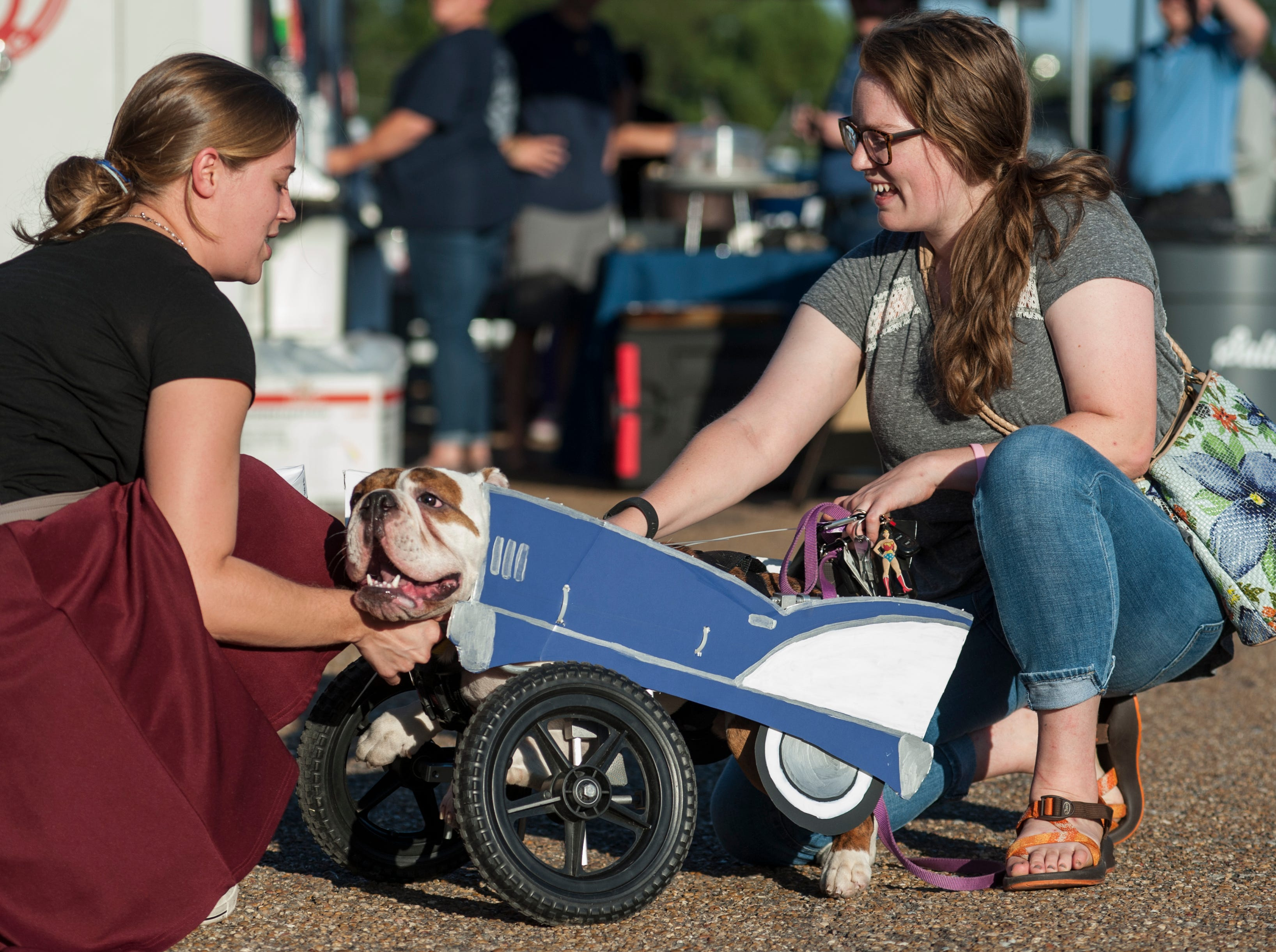 Caitlin Price left, of Brandon, and her sister Lana Mize, right, of Jackson, loves on Mize's dog, Linus, who is dressed as a car and showing off his wheels, all ready for the Halloween pet costume contest at Fondren After Five.