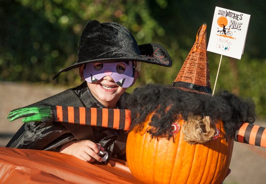 Finley Warden, 5, of Jackson, poses proudly by his award-winning pumpkin decorating contest entry duirng the October Fondren After Five. Preceeds from the contest go to the nonprofit Extra Table.