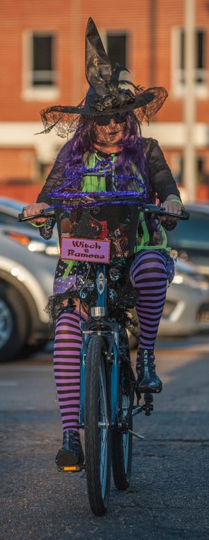 Witch Kelly Wulf-Stuart, of Madison, tests out the logistics of riding in full regalia before heading out with the group during the first annual Witches Ride benefiting Extra Table.