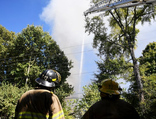 Jackson firefighters watch one of their aerial ladder trucks spray water onto a home on fire, Thursday, October 18, 2018, at the corner of Wallace Road and Hollywood Drive. Students at Empire Beauty School saw the fire and ran to the house to alert the people inside by blowing on the horn of the unlocked car in the driveway.