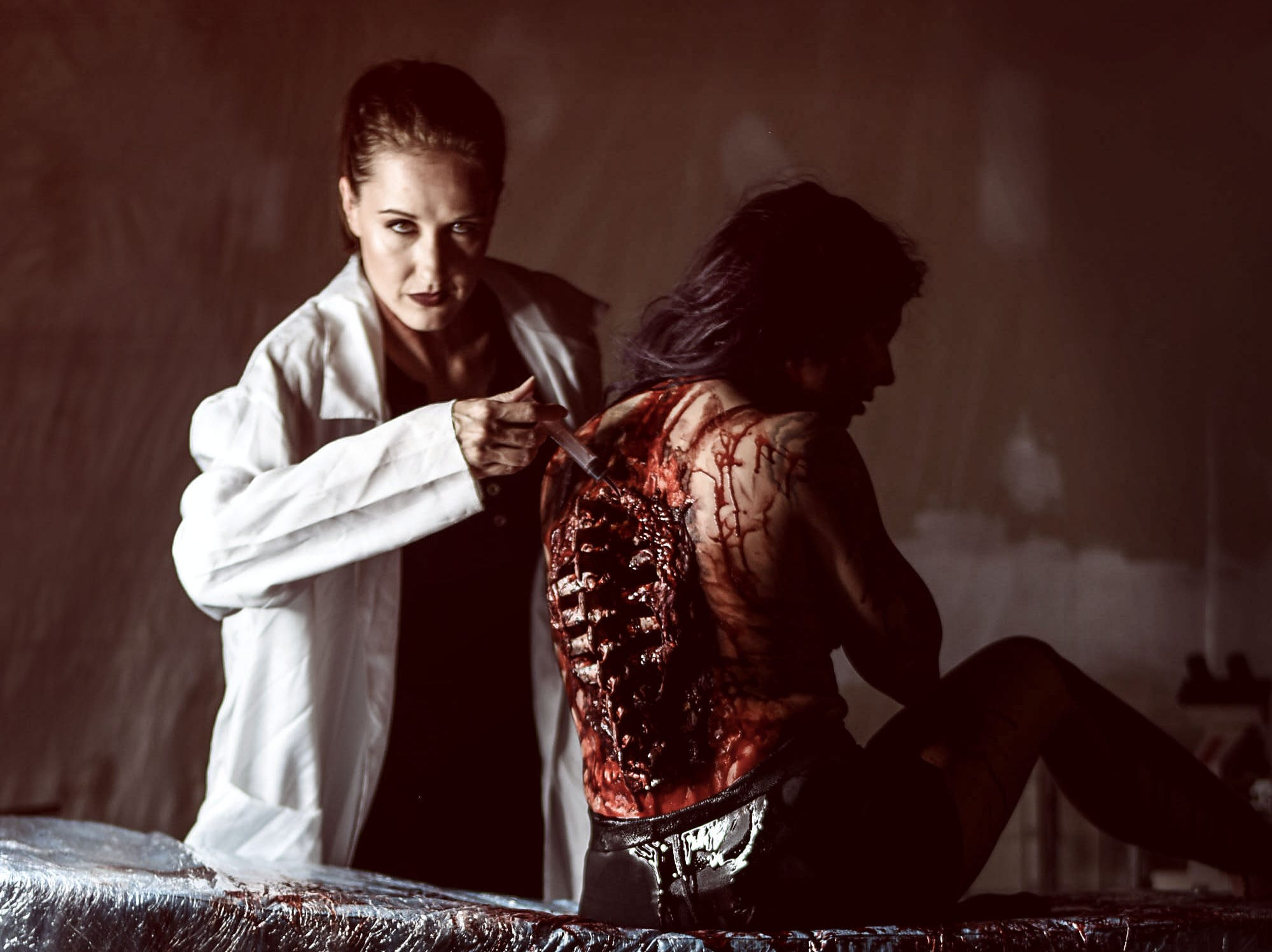 Lori Cannon portrays a mad physician with Leighann Word as the victim in this horror-themed photo session by Mallory Bertrand. Special effects by Ash Mac.