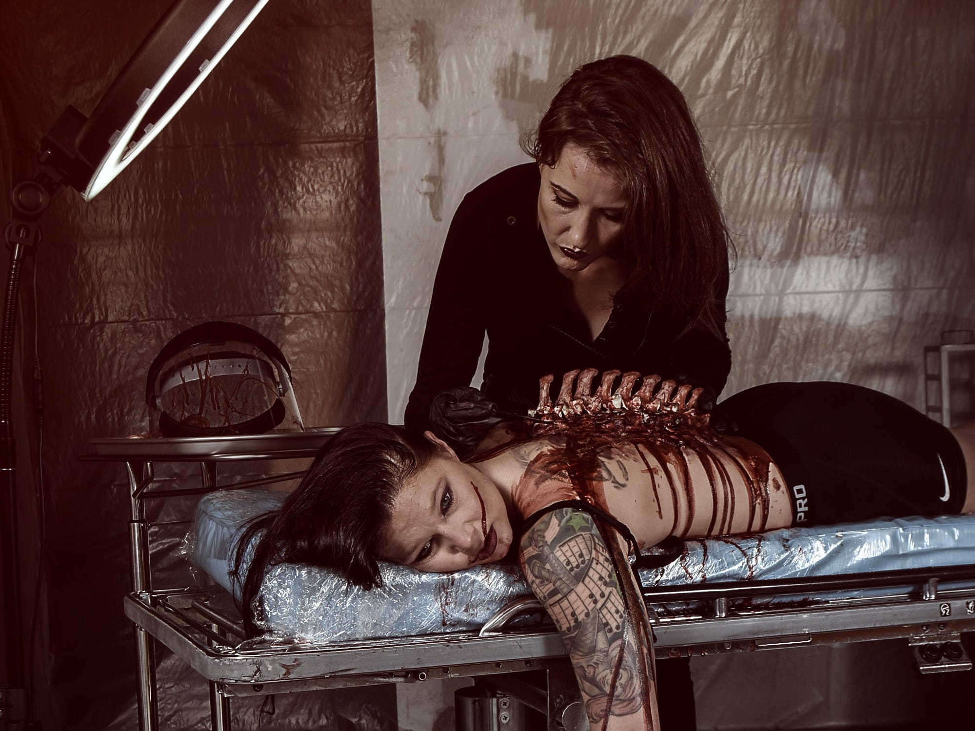 Lori Cannon portrays the physician with Leighann Word as the victim in this horror-themed photo session by Mallory Bertrand. Special effects are by Ash Mac.