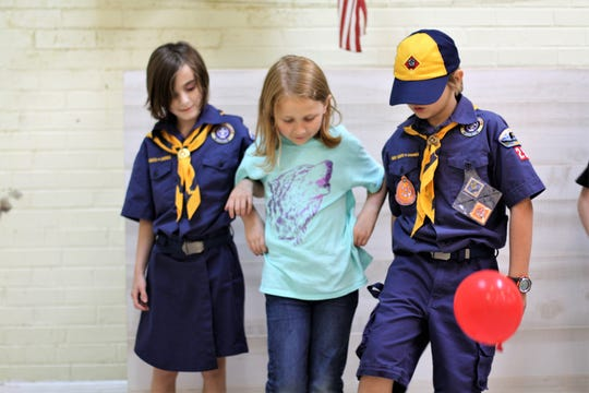 Wolf Den members Rowan Headlee, Sadie Greene and Bowman Gambino participate in a balloon activity at Troop 25's meeting at First Presbyterian Church in Fountain City.