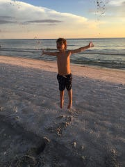 Spencer, 6, on the beach the month before being diagnosed with acute flaccid myelitis that left him unable to move his legs.