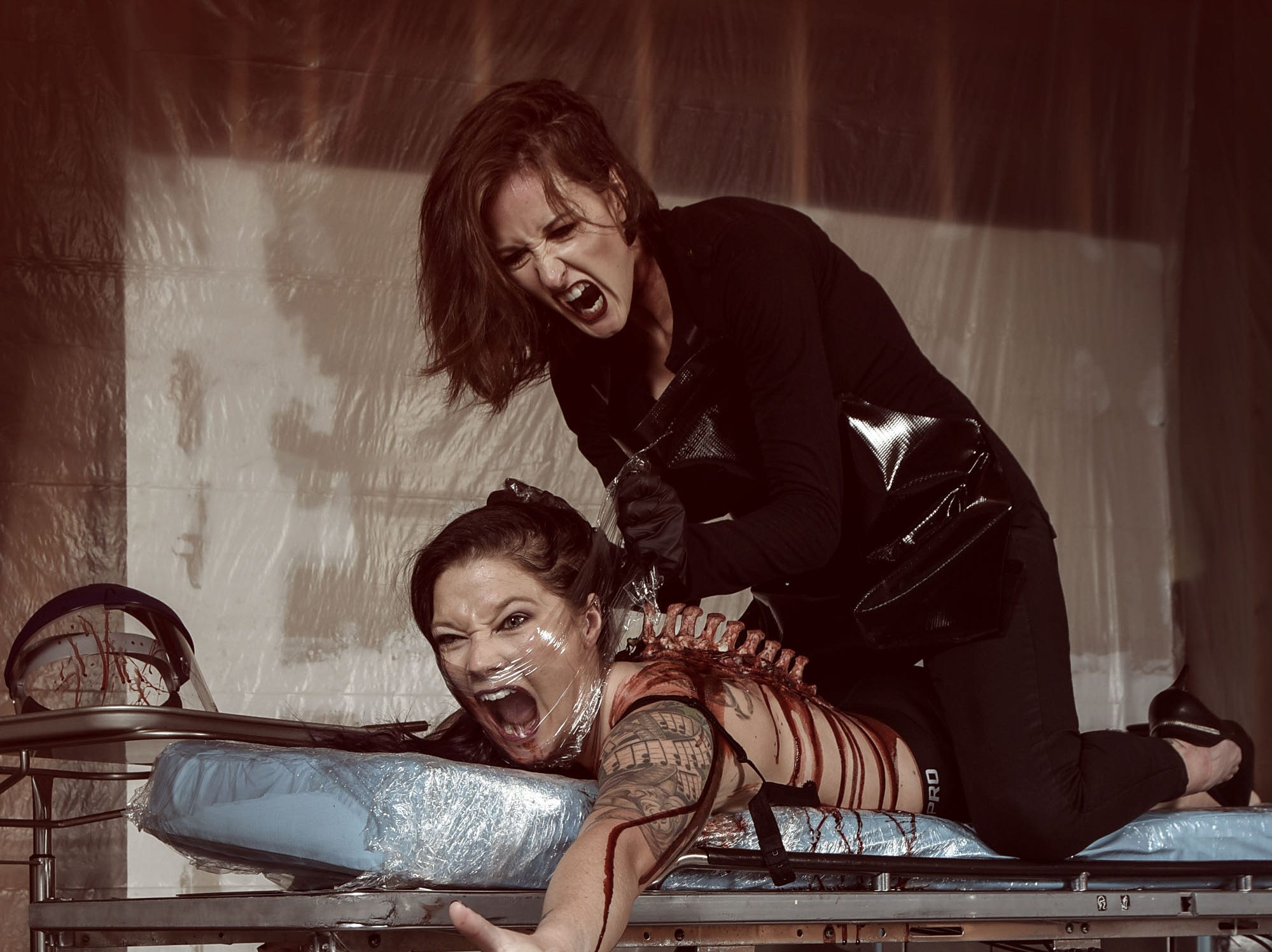 Lori Cannon portrays the mad physician with Leighann Word as the victim in this horror-themed photo session by Mallory Bertrand. Special effects by Ash Mac.