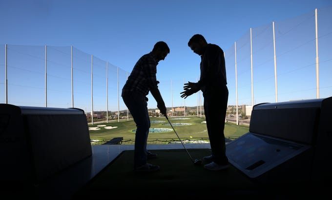 Courier Journal reporter Justin Sayers, left, got instruction from lead instructor Zach Gerlach at the Topgolf outside of Cincinnati, Ohio.  Topgolf is proposing to build a facility at the Oxmoor Center in Louisville as they wait for a decision by the Louisville Metro Planning Commission. 