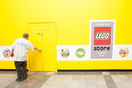 The door in the barricade at the front of the new LEGO store in Oxmoor Center is closed by a workmen who had been inside it preparing for the store's opening. 