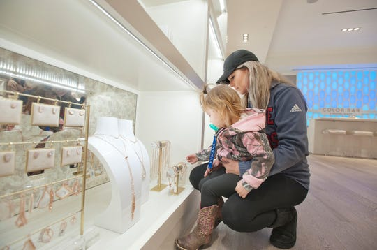 Alex Jewell of Lanesville watches as her daughter, Charlotte Sharp, age 2, checks out a necklace in the Kendra Scott women's jewelry and gifts store at Oxmoor Center.