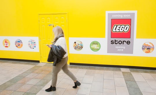 A mall shopper passes the  barricade at the front of the new LEGO store in Oxmoor Center where workmen inside are preparing for the store's opening. October 18, 2018