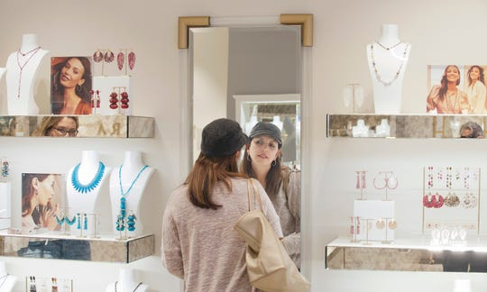 Angelica Ramirez, of Prospect, tries on some earrings in the Kendra Scott women's jewelry and gifts store at Oxmoor Center.