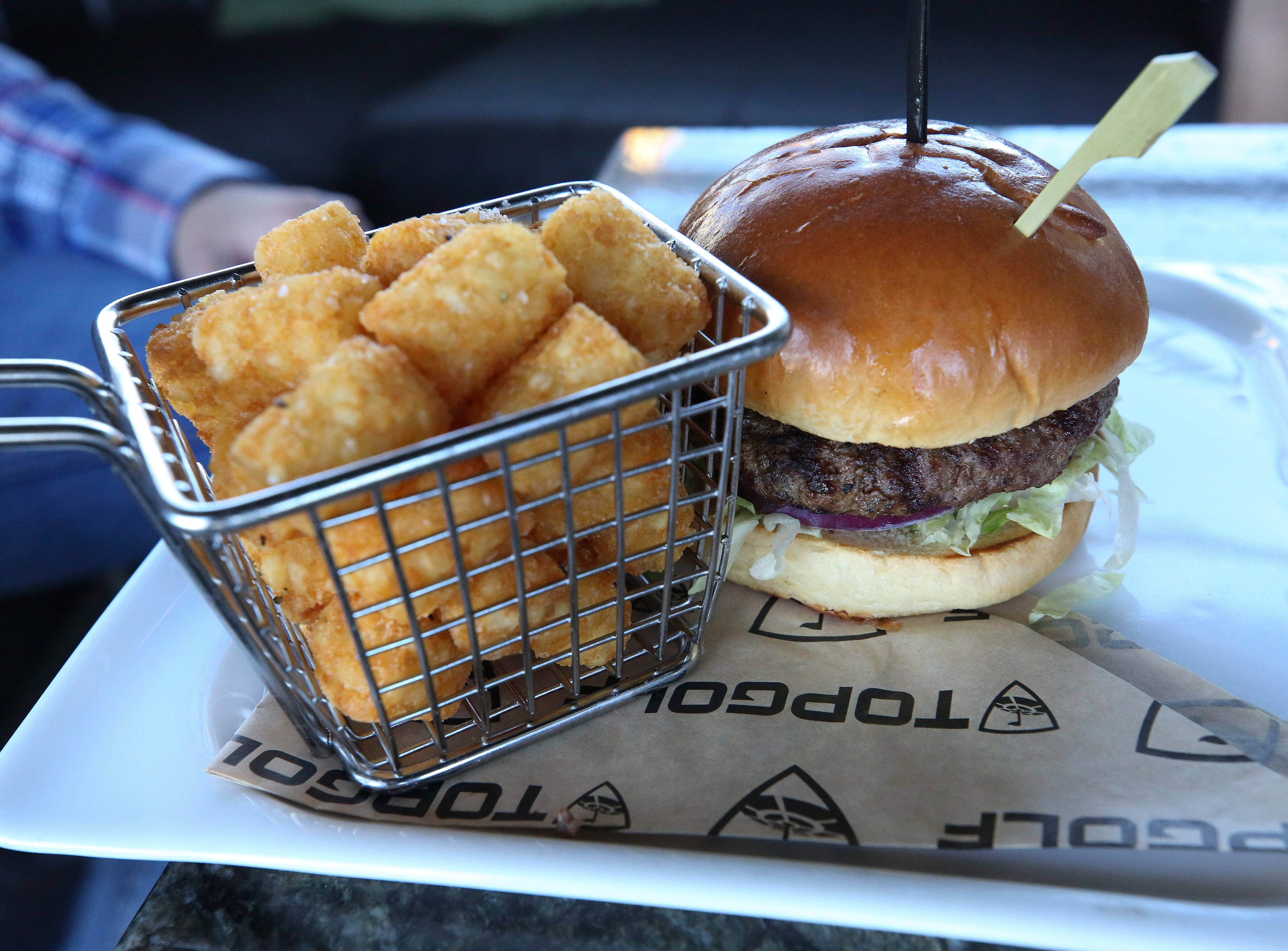 A hamburger and tater tots served at the Topgolf outside of Cincinnati, Ohio.  Topgolf is proposing to build a facility at the Oxmoor Center in Louisville as they wait for a decision by the Metro planning commission. 