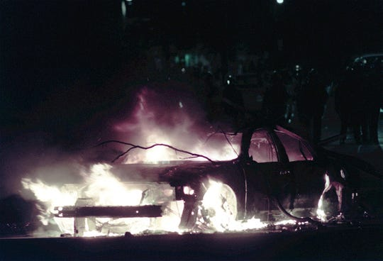 A police car burns on Bogue street in East Lansing during a riot in 1999.