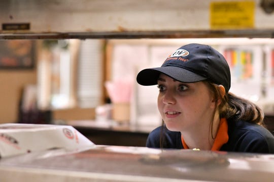 Jesika Price, 19, of Grand Ledge, chats with Grand Ledge A&W co-workers, while waiting for her food at the window, Thursday, Oct. 18, 2018.