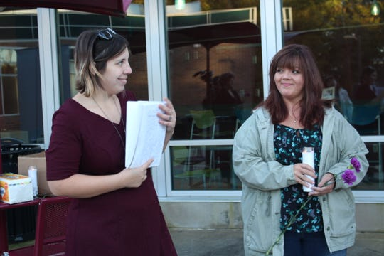 Domestic violence survivors Brittany Ludwig, left, and Kim Williams, right, smile at each other after Ludwig shared her story during a candlelight vigil Thursday, Oct. 18, 2018. October is Domestic Violence Awareness Month.
