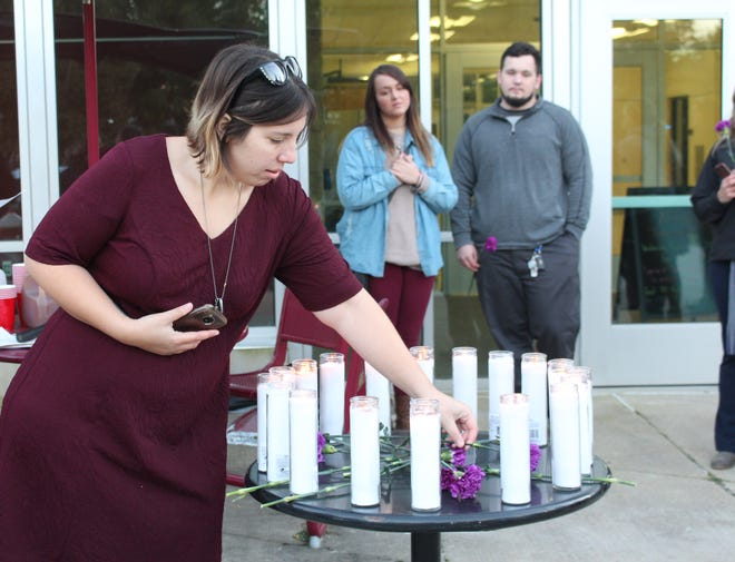 Domestic violence survivor Brittany Ludwig places a purple carnation to remember someone who lost their life to domestic violence during a candlelight vigil Thursday, Oct. 18, 2018. October is Domestic Violence Awareness Month.