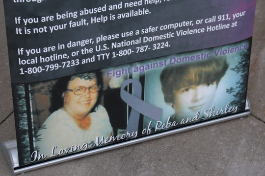 A banner displays photos of Shirley Carver and Reba Dickison, who lost their lives to domestic violence, during a candlelight vigil Thursday, Oct. 18, 2018. Kim Williams, Carver's daughter and Dickison's granddaughter, was there when they were shot and killed.
