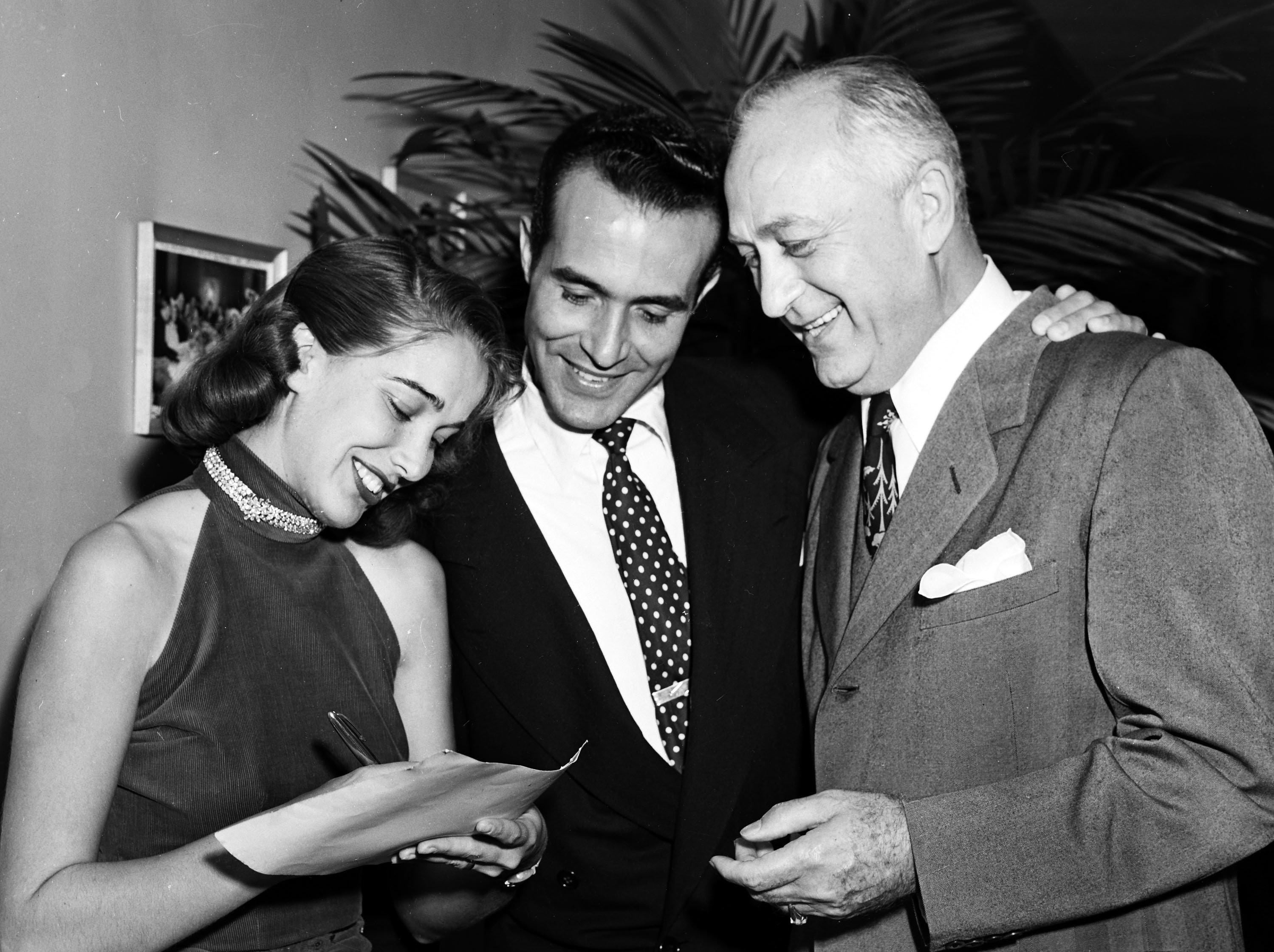 Pert Julia Adams, who went to Hollywood from Little Rock, autographed a picture for the Variety Club in October 1951.  Naturally pleased was M.A. Lightman (Right), president of Malco, Inc. Waiting his turn was Ricardo Montalban of Hollywood.