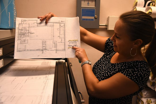 Purchasing and Risk Manager Lina Upham shows the original plans drawn by architect Herb Savage, inside the vault, left over from the building's years as a bank. The City of Marco Island is holding an open house Tuesday afternoon at City Hall, from 3 to 5 p.m.