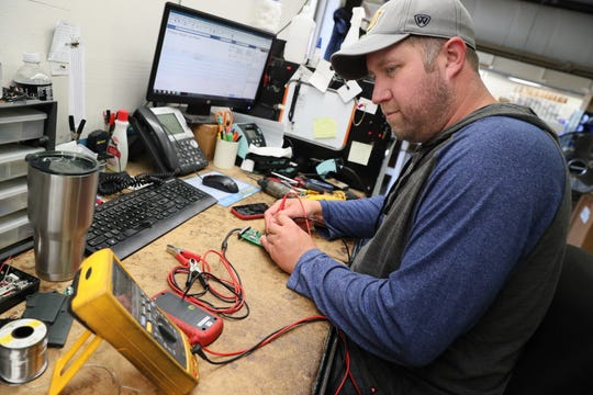 Jason Hamholm repairs a relay tester at Electronic Specialties in Genoa City.  The company has been hit with a 25 percent tariff on products from China, seriously hurting the business and many others like it.