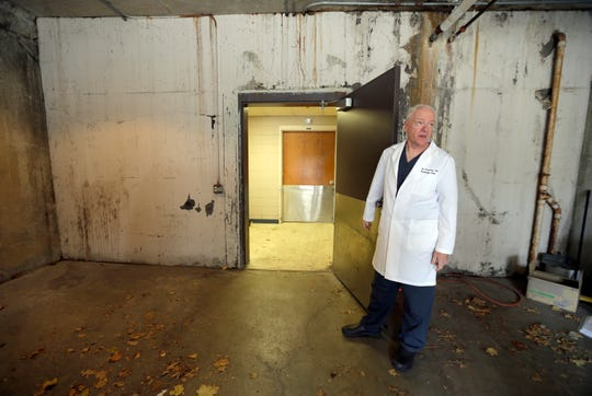 Milwaukee County Chief Medical Examiner Brian Peterson shows extensive water damage in basement receiving area of the office at 933 W. Highland Ave. in December 2015.