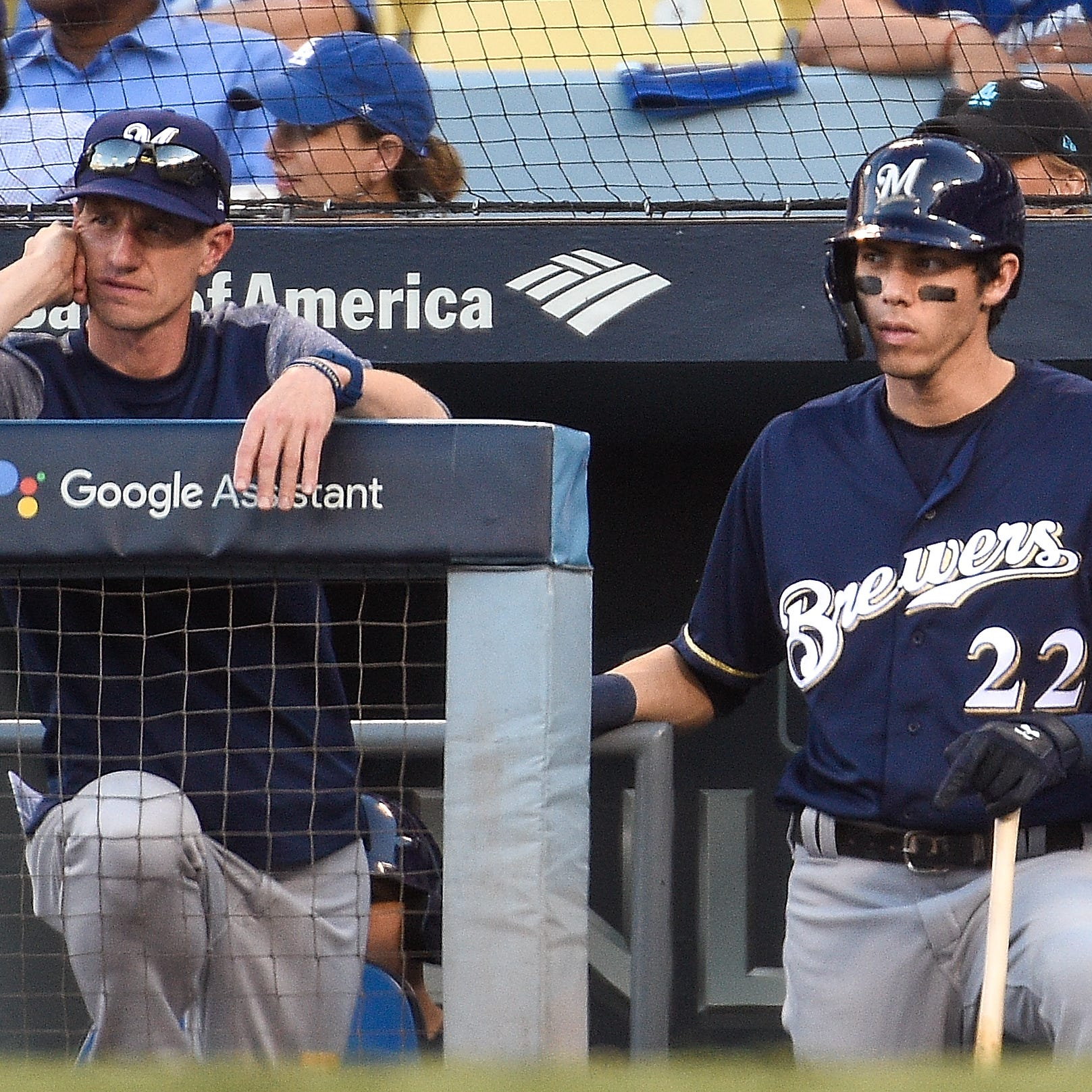 Craig Counsell and Christian Yelich watch from...
