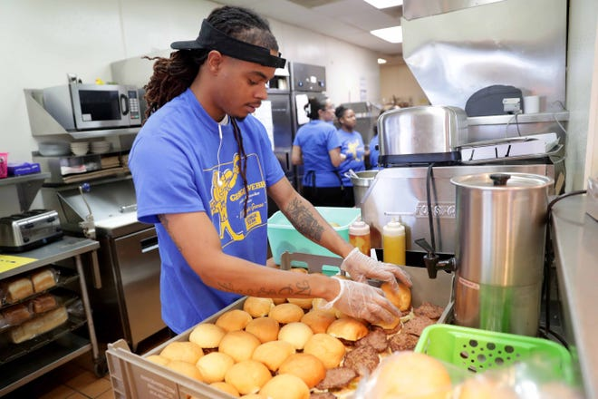 A cook at a George Webb restaurant prepares free hamburgers last October to mark the Milwaukee Brewers' 12-game winning streak. Wisconsin's latest employment numbers show strong gains in leisure-and-hospitality jobs such as those at restaurants.