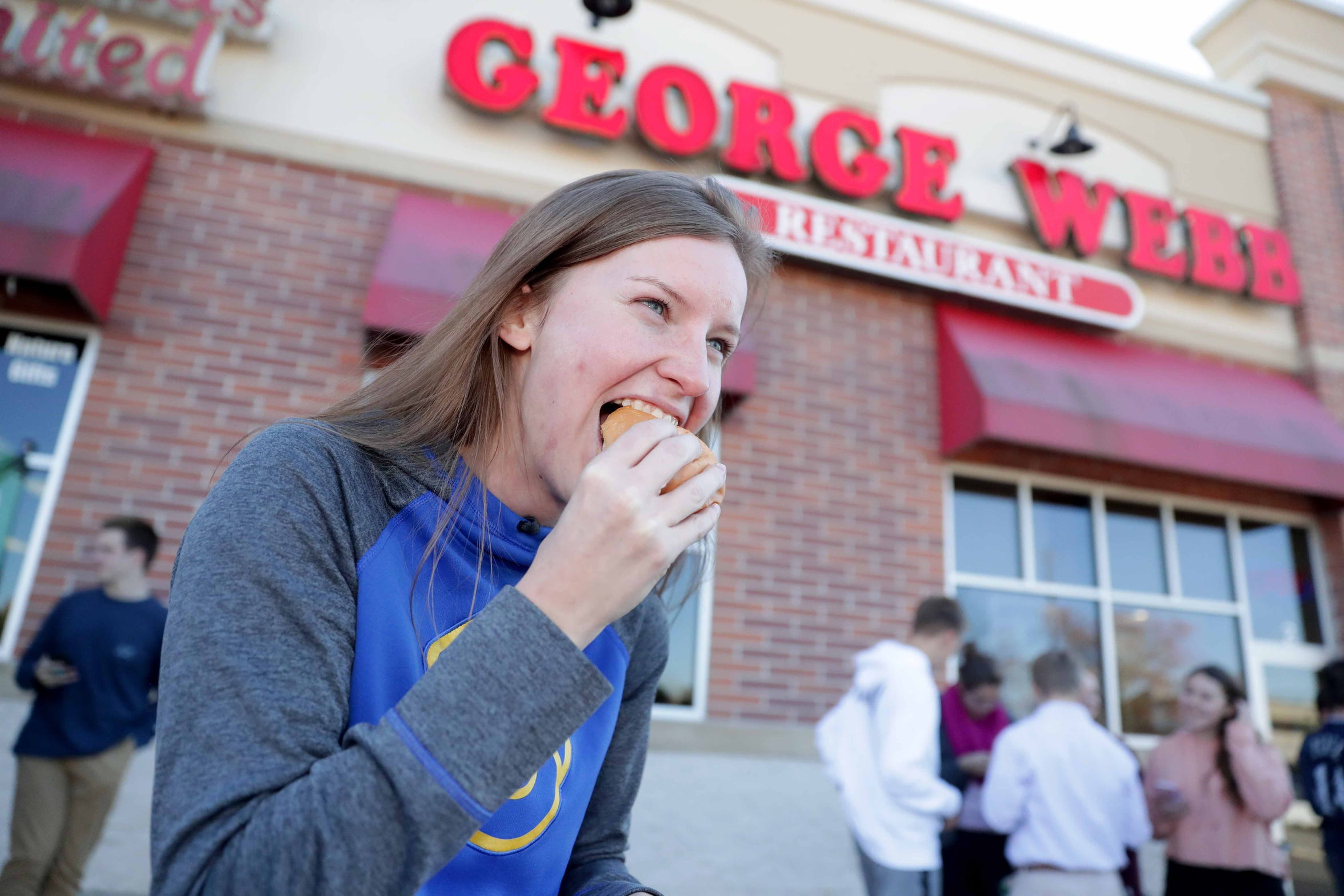 Lauren Wysocki of Pewaukee takes a bite out of her free hamburger at the George Webb Restaurant in Brookfield, where she was with her mother, Sandy Wysocki. George Webb Restaurants across the state handed out free hamburgers on Thursday, delivering on the promise it made if the Brewers won 12 games in a row. The restaurant allowed one burger per customer.