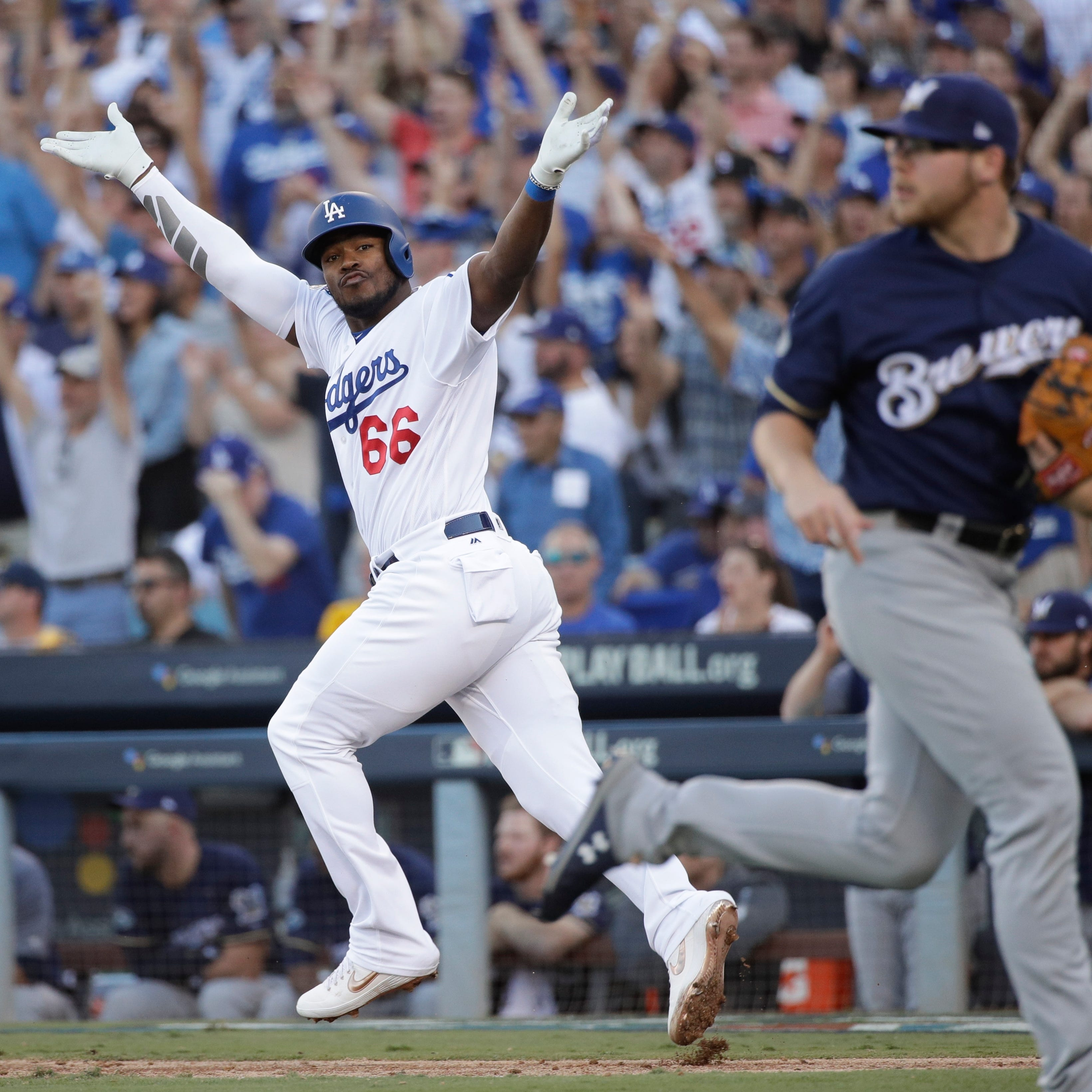 Los Angeles Dodgers' Yasiel Puig reacts after...