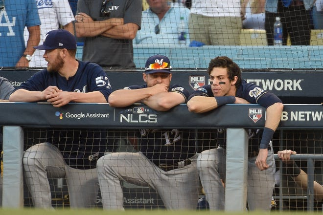 Milwaukee Brewers pitcher Jimmy Nelson (52), catcher Stephen Vogt (12) and  Christian Yelich #22 react during the ninth inning against the Los Angeles Dodgers in Game Five of the National League Championship Series at Dodger Stadium on October 17, 2018 in Los Angeles, California.