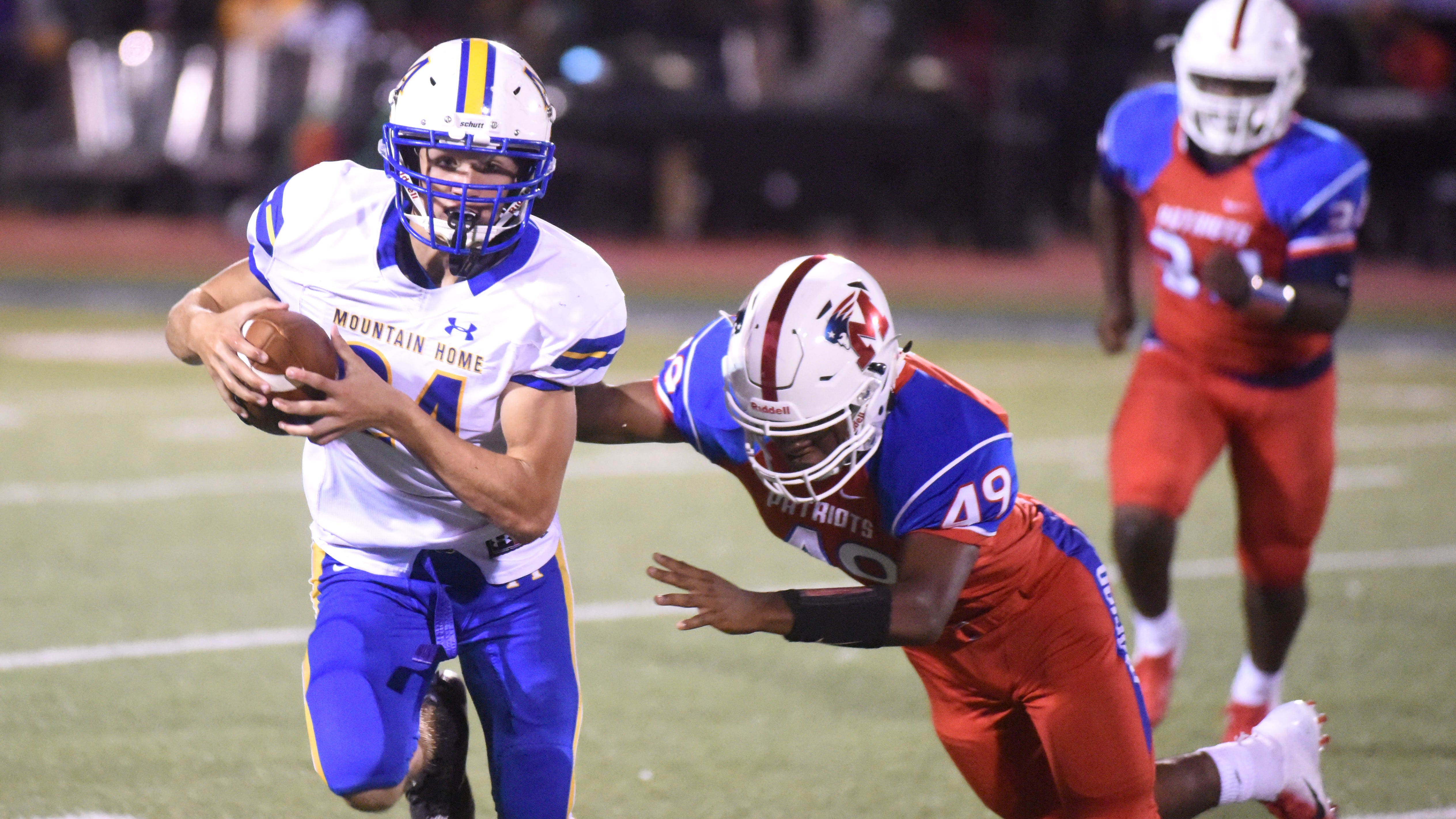 Mountain Home's Lawson Stockton runs past a Marion defender during last week's game at Marion.