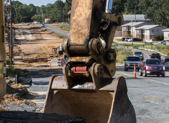 Cars pass the continuing construction work along Arkansas Road in West Monroe, La. on Oct. 18. Construction starts at North 7th Street and continues about 3 miles west to Caldwell Road as the Louisiana DOTD seeks to widen the road and add roundabouts along the route to ease traffic and congestion.
