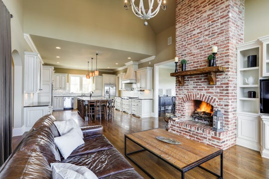 The centerpiece of this living room is a massive brick, wood-burning fireplace.