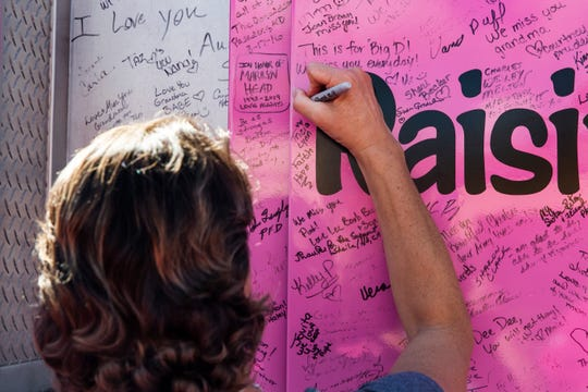 Tricia Leckbee signs the Pink Heals firetruck during a surprise fundraiser organized by her friends, family and coworkers with the national nonprofit organization in front of Aerie Lane in Bonita Springs on Thursday, Oct. 18, 2018.