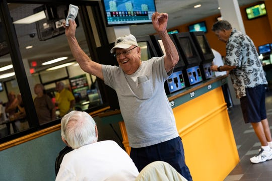 """Larry Campbell of Cape Coral rejoices his second win of the day by shaking his earning in the air. Campbell won $48 the first time and $12.40 the second time round. """"I bet because it is entertaining,"""" he said."""