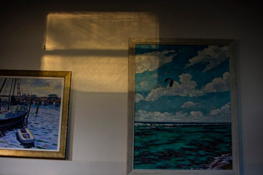 Phil Fisher's paintings hang on the wall of Phil Fisher Gallery during the season's first Galleries of Crayton Cove art walk, called Art After Dark, on Saturday, Oct. 13, 2018.
