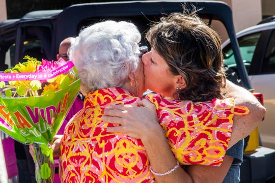 Tricia Leckbee kisses her mother, Peggy White, during a surprise fundraiser organized by her friends, family and coworkers with Pink Heals, a national nonprofit organization, in front of Aerie Lane in Bonita Springs on Thursday, Oct. 18, 2018.