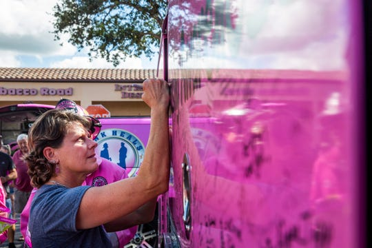 Tricia Leckbee signs the Pink Heals firetruck during a surprise fundraiser organized by her friends, family and coworkers in front of Aerie Lane in Bonita Springs on Thursday, Oct. 18, 2018. The truck is only signed by those who have survived cancer, are currently battling cancer or in memory of those who have died from cancer.